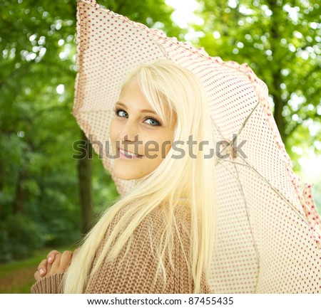 Young sexy blonde woman holding umbrella looking teasingly over her shoulder as she flirts in park. - stock photo