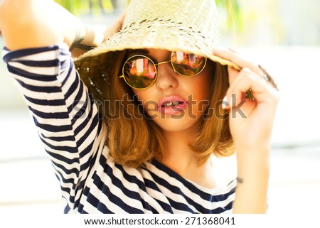 Young sexy blonde woman posing in the park, wearing jacket, floral hat mirrored sunglasses and bright make up, Lifestyle portrait bright toned colors. - stock photo