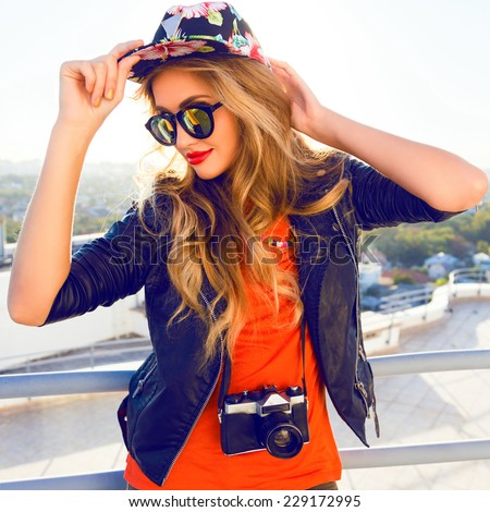 Young sexy blonde woman posing in the roof, wearing leater jacket, swag floral hat mirrored sunglasses and bright make up, holding vintage camera, Lifestyle portrait bright toned colors. - stock photo