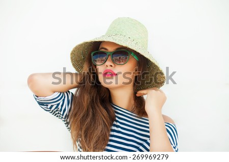 Young sexy blonde woman posing in the white wall, wearing  frock, swag hat mirrored sunglasses and bright make up,show emotions,Lifestyle portrait bright toned colors.Summer Reflecting Sunglasses,hat. - stock photo