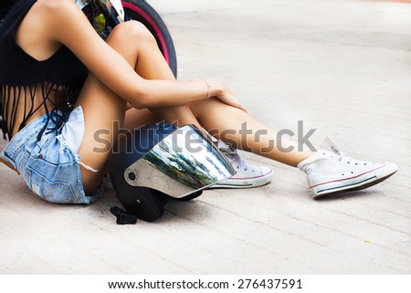 Young sexy blonde woman sitting on the street,with helmet opposite motorbike.Lifestyle portrait bright toned colors,cool rock n roll girl, wear summer outfit, bright summer clothes,denim shorts - stock photo