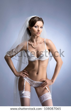 Young sexy bride in erotic lingerie over blue - stock photo