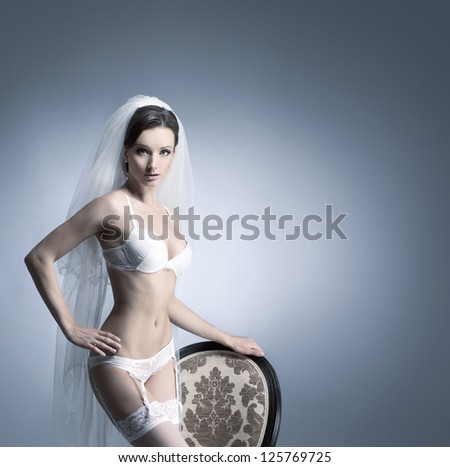 Young sexy bride in erotic lingerie over blue background with some blank space - stock photo
