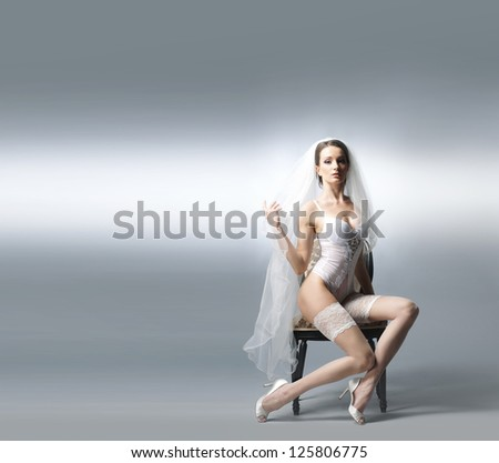 Young sexy bride in erotic lingerie over grey background with a lot of blank space - stock photo