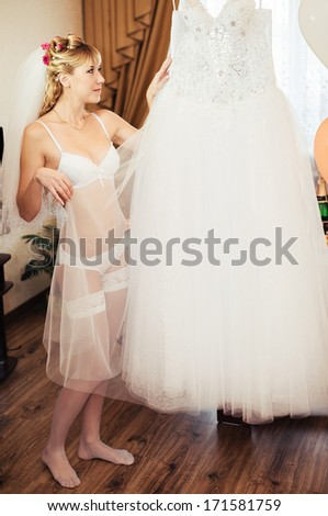 Young sexy bride in erotic lingerie over window - stock photo