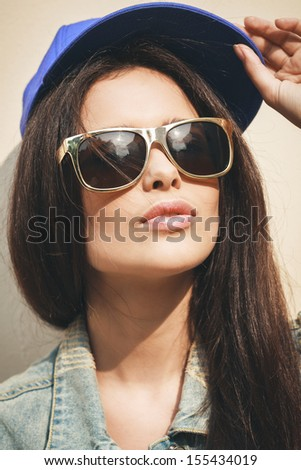 Young sexy brunette girl closeup portrait. Stylish woman posing with interested look and sunglasses and  cap on her head. - stock photo