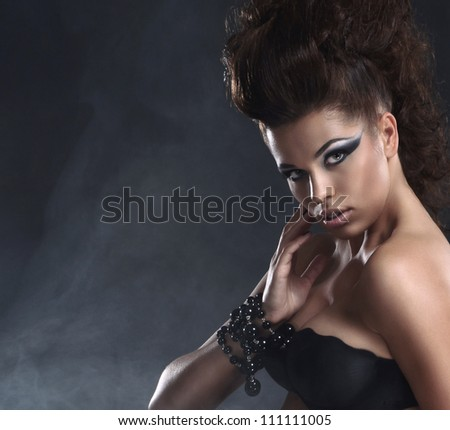 Young sexy brunette over black background with smoke - stock photo