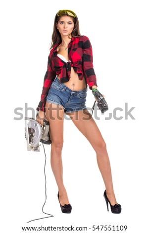 Young sexy brunette woman holding a construction drill and Circular Saw