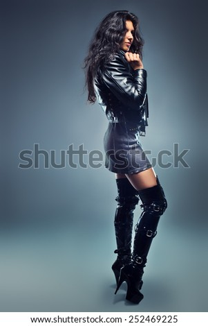 Young sexy brunette woman in leather clothing on wall background. - stock photo