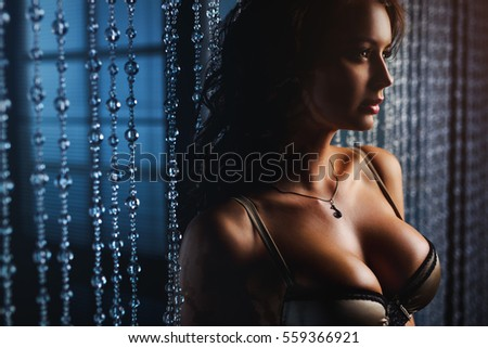 Young sexy brunette woman looking aside portrait. Focus on breast.