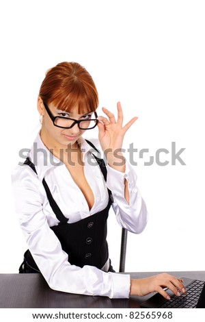young sexy business woman with red hair with black glasses sitting at the table with laptop
