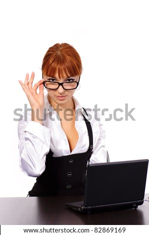 young sexy business woman with red hair with black glasses sitting at the table with laptop isolated on white