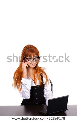 young sexy business woman with red hair with black glasses sitting at the table with laptop and mobile phone isolated on white