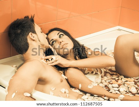 young sexy couple enjoy each other in bathroom of roses - stock photo