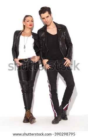 young sexy couple in leather jackets posing, standing against white wall