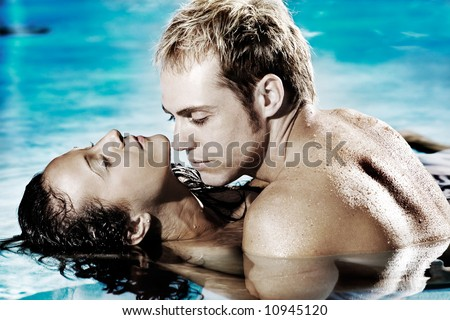 Young sexy couple in pool holding each other - stock photo