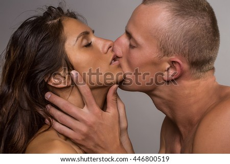 young sexy couple of handsome man embracing and kissing naked pretty woman has long hair with bare shoulders on grey background