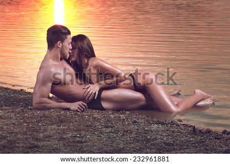 Young sexy couple on beach topless at sunset..Fashion colors.