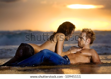 Young sexy couple on beach topless in jeans - stock photo