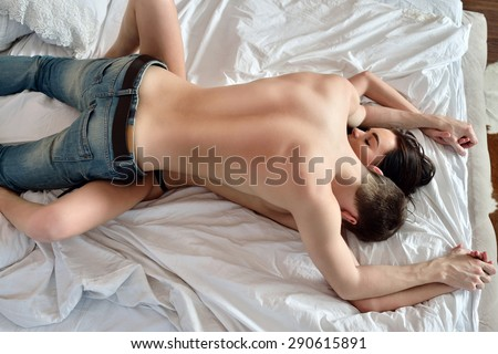 Young sexy couple on the bed. Beautiful lady and guy in erotic pose. Portrait of girl and boy indoors. Beauty woman with attractive buttocks in lace lingerie. Female ass in underwear. Naked models - stock photo