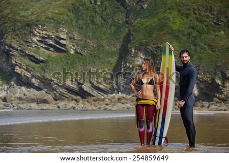 Young sexy couple standing at the beach, ready to surf in a summer day, surfer couple with attractive young girl and handsome young man standing with surfboard waiting for good waves - stock photo