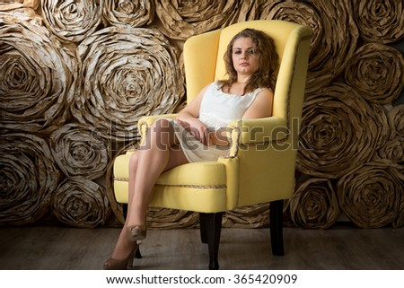 Young sexy curly woman posing in bug yellow armchair - stock photo