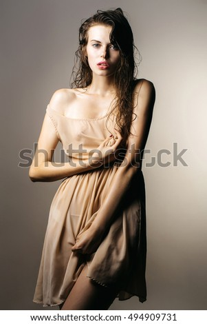 young sexy fashionable woman or girl with long brunette wet hair and pretty face in stylish beige dress in studio on grey background