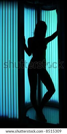 Young sexy female in a tanning cabin, shoot for shape against a light - full body length version. - stock photo