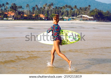 Young sexy fit happy woman running with surf board at California beach, nice sunny day, bright colors. - stock photo