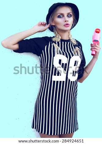 Young sexy girl.Fashion portrait of young beautiful woman in cap.Bright background.Outdoor lifestyle portrait.Swag style in fashionable clothes.Respirator.Face mask.Pink gun.Make up. - stock photo