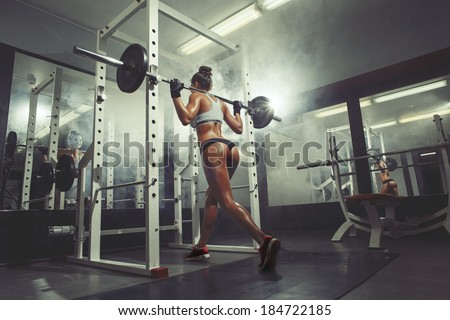 Young sexy girl in the gym doing squat on smoke background - stock photo