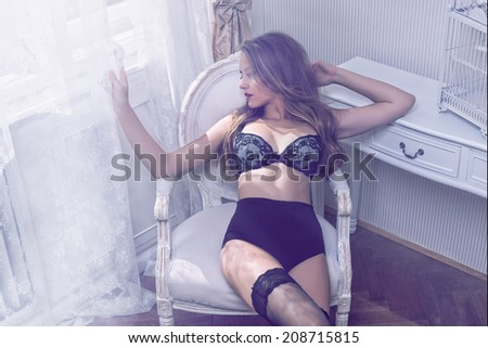 Young sexy girl sitting on antique chair and looking out of window - stock photo