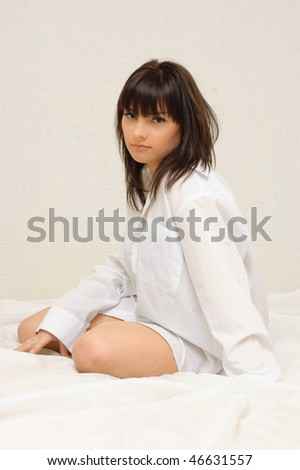 Young sexy girl sitting on her bed in a white shirt - stock photo