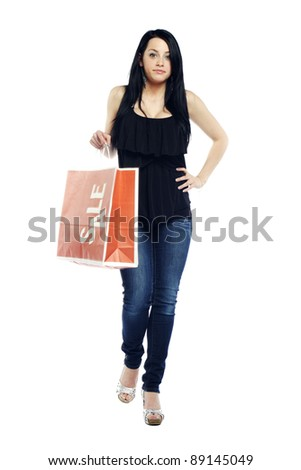Young sexy girl walking with shopping bag against white background - stock photo