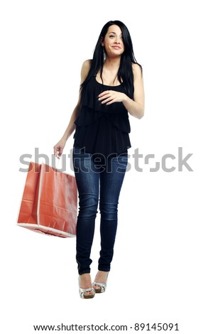 Young sexy girl walking with shopping bag laughing against white background - stock photo