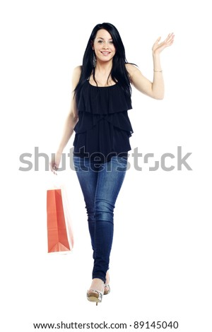 Young sexy girl walking with shopping bag waving to the camera - stock photo