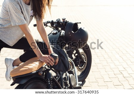 Young sexy girl with cup of coffee and  vintage custom motorcycle. Outdoor lifestyle portrait
