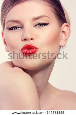 Young sexy girl with retro red lips. Beautiful blond Caucasian female kissing. - stock photo
