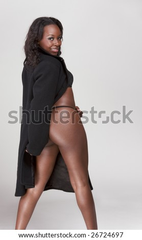 Young sexy gorgeous black African American female in black provocative suggestive lingerie and coat, exposing her buttocks - stock photo