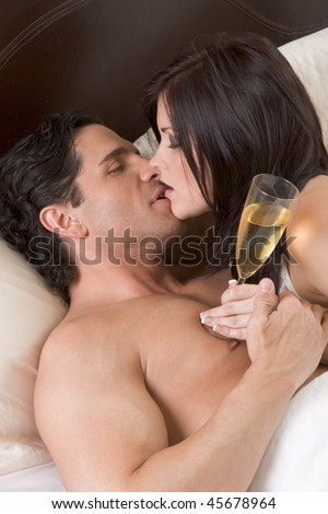 Young sexy heterosexual couple celebrating with wine in bed