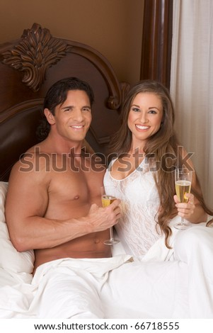 Young sexy heterosexual couple celebrating with wine in bed - stock photo