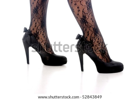 Young sexy lady in her high heels standing on white background - stock photo