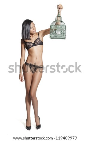 Young sexy latin woman in underwear holding a bird cage. On white background. - stock photo