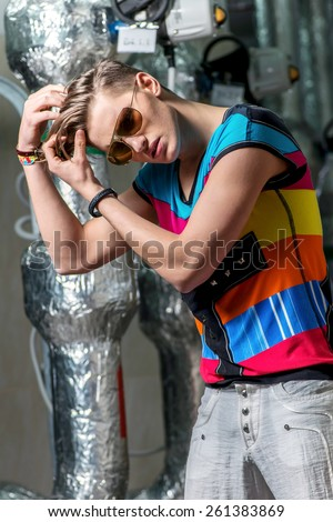 Young sexy male model posing for the camera in sunglasses standing alone in pipeline.Cute and fashionable young man smiling. Portrait of a confident male model. Summer men's image with a slim figure - stock photo