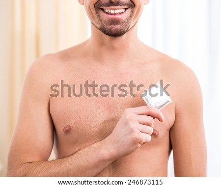 Young sexy man holding condom in hand - stock photo