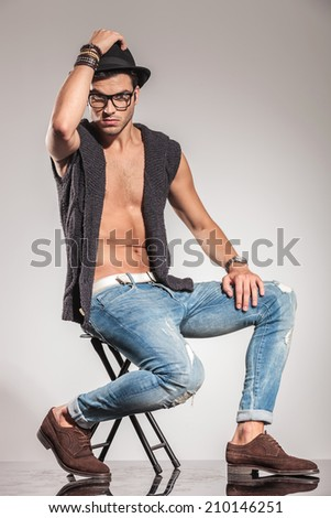 young sexy man in a fashion pose with hand on his hat, sitting on a chair on grey studio background - stock photo