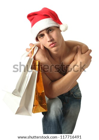 Young sexy man in Santa Claus hat with shopping bags isolated on white - stock photo