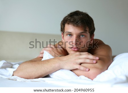 Young sexy man lying on the bed - stock photo