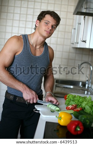 Young sexy man preparing salad at the kitchen - stock photo