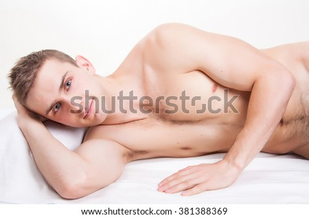 Young sexy man with a naked torso is isolated on a white background